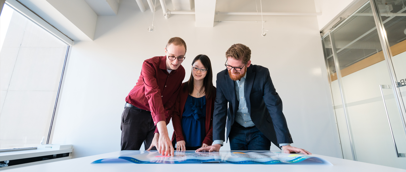 people standing over blueprints on a desk
