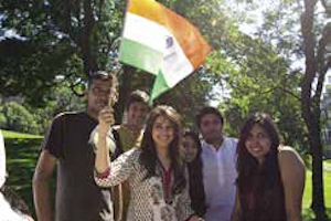 A group of students from the Indian Students Association pose with an Indian flag.