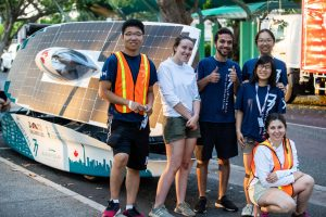 A group of students stand in front of a solar car.
