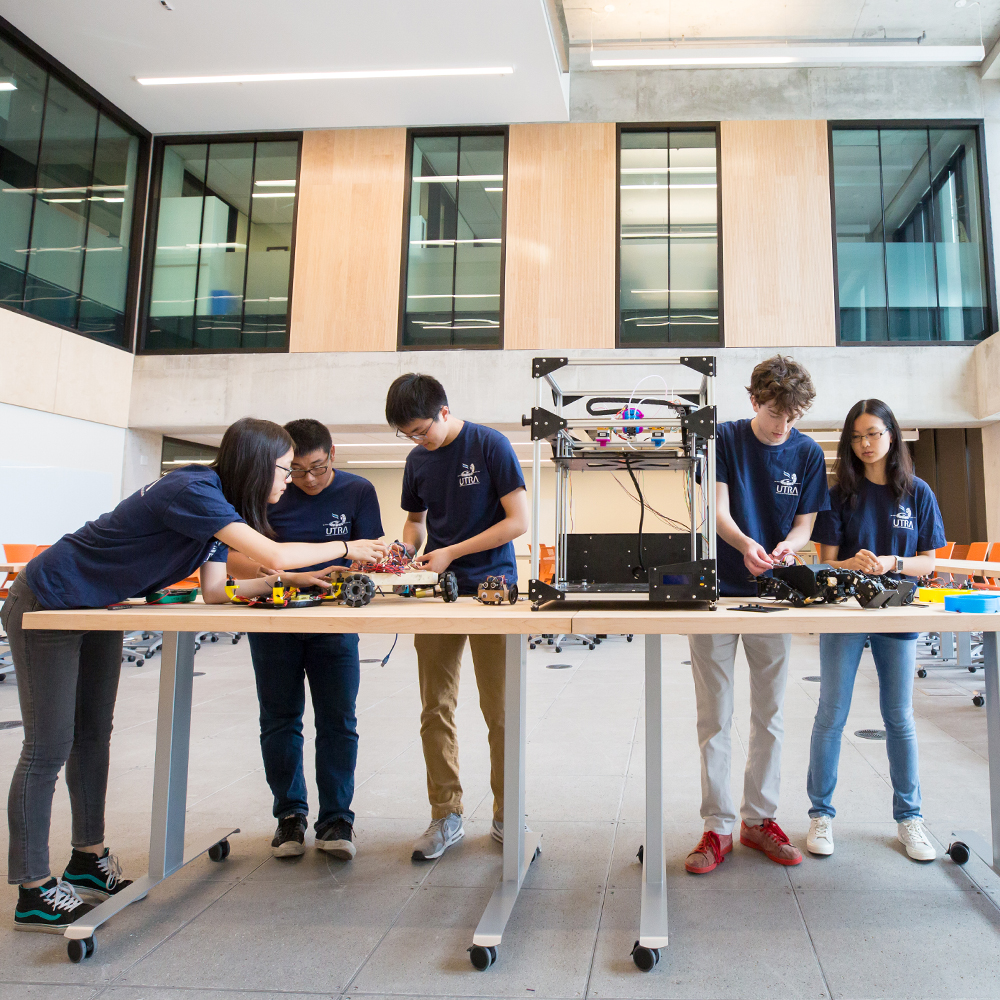 students working with machinery at table